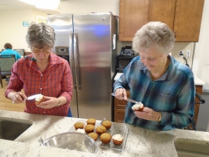 Two enhanced assisted living residents frost cupcakes together.