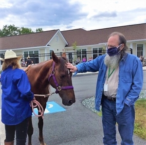 An assisted living resident pats a horse that was brought to campus.